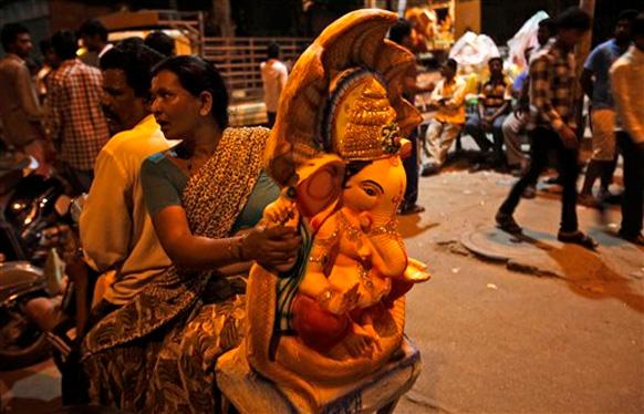 हैदराबाद में भगवान गणेश की प्रतिमा पूजा के लिए ले जाते श्रद्धालु।