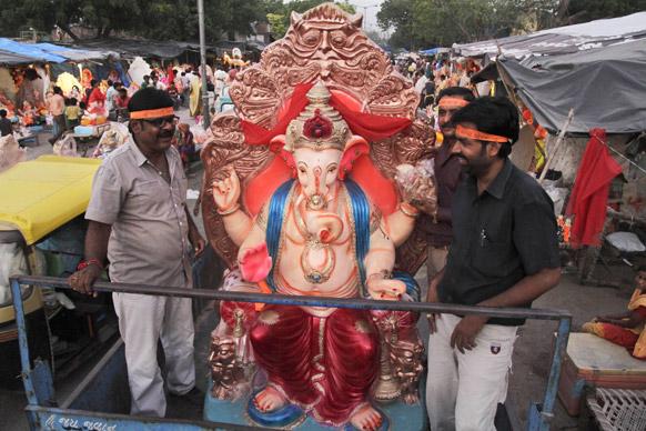 अहमदाबाद में भगवान गणेश की प्रतिमा को पूजा के लिए ले जाते श्रद्धालु।