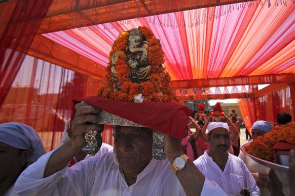 जम्मू में भगवान गणेश की प्रतिमा को सर पर उठाकर ले जाते श्रद्धालु।