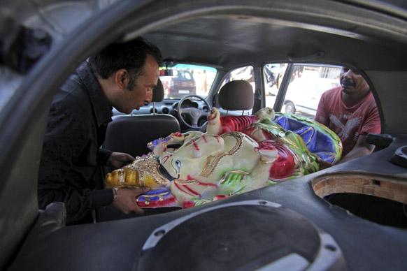 जम्मू में हिंदू भगवान गणेश की प्रतिमा को कार में ले जाते हुए श्रद्धालु।