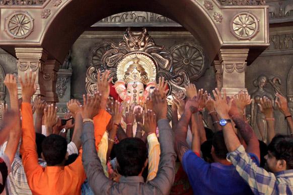 मुंबई में गणेश चतुर्थी के त्योहार के दौरान श्रद्धालु हाथ उठाकर गणपति की पूजा करते हुए।