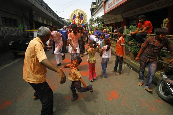 मुंबई में गणेश चतुर्थी त्योहार के दौरान हिंदू श्रद्धालु डांस करते हुए।