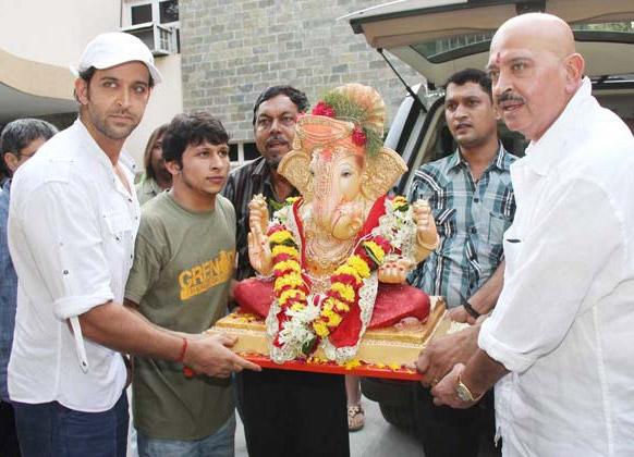 भगवान गणेश की प्रतिमा को घर लाते हुए अभिनेता राकेश रोशन और रितिक रोशन।