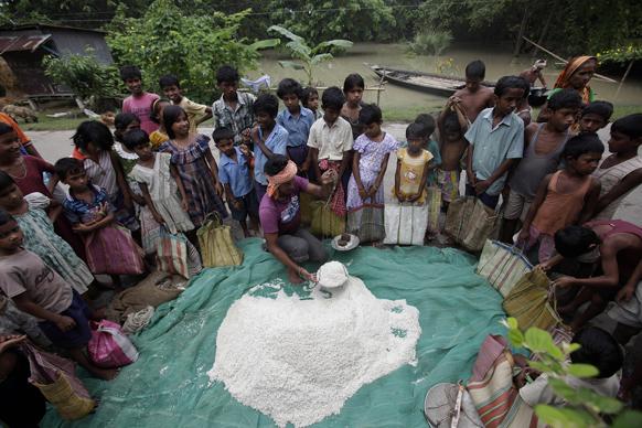 असम में बाढ़ से प्रभावित लोगों के बीच राहत सामग्री दिया जा रहा है।