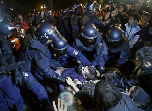 मैड्रिड में विरोध-प्रदर्शन को रोकते पुलिसकर्मी।