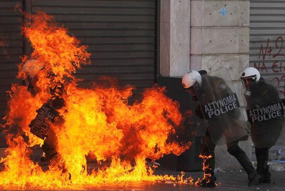एथेंस में प्रदर्शानकारियों ने एक कार में आग लगा दी।