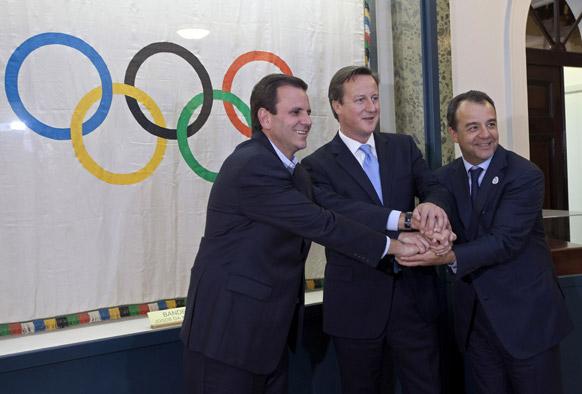 ब्राजील की राजधानी रियो डि जनेरियो में ओलम्पिक ध्वज के सामने पोज देते ब्रिटेन के प्रधानमंत्री डेविड कैमरन (मध्य में), रियो डि जनेरियो के गवर्नर सर्जियो कैबराल (दाएं) और रियो डि जनेरियो के मेयर एडुआर्डो पेस।