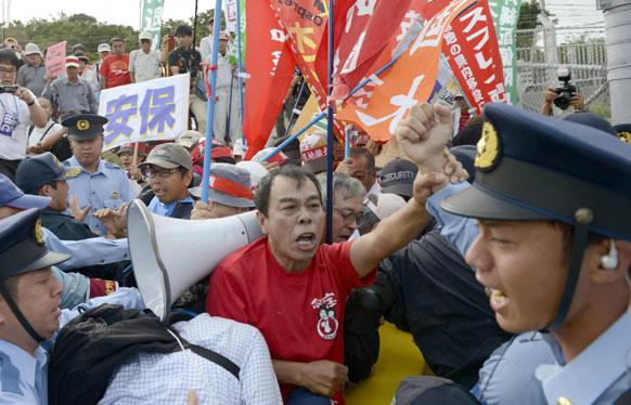 जापान के दक्षिणी शहर ओकिनावा में एमवी-22 लड़ाकू विमान की तैनाती का विरोध करते स्थानीय नागरिक।