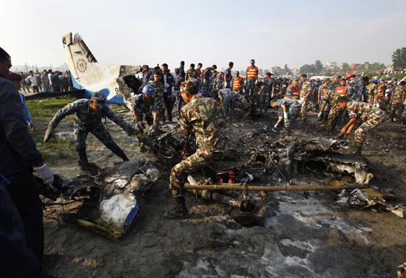 काठमांडू के समीप सीता एयर के दुर्घटनाग्रस्त विमान के मलबे को हटाते पुलिसकर्मी। इस हादसे में कुल 19 लोग मारे गए।