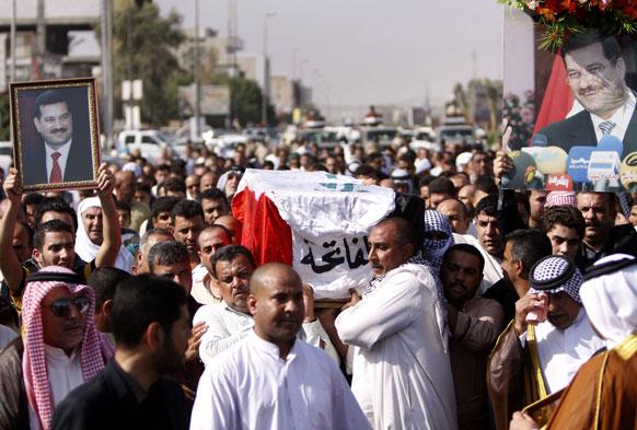 इराक के बसरा में पूर्व गवर्नर मोहम्मद अल-वाली का जनाजा निकालते उनके करीबी।