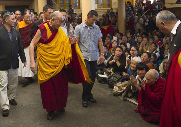 धर्मशाला में एक प्रार्थना समारोह के बाद श्रद्धालुओं का अभिवादन स्वीकार करते तिब्बती आध्यात्मिक गुरु दलाई लामा।