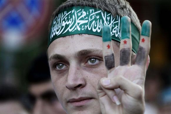 लेबनान मे एक व्यक्ति माथे पर पट्टी और उंगलियों के निशान के जरिए प्रदर्शन करता हुआ।