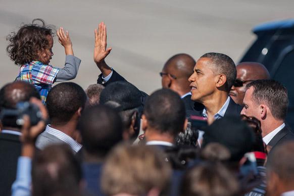 न्यूपोर्ट में यूएस राषट्रपति बराक ओबामा एयरपोर्ट पर बच्चे से हाथ मिलाते हुए।