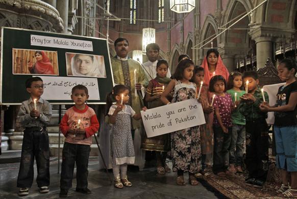लाहौर में मलाला यूसुफजई के लिए कैंडल प्रार्थना करते स्कूली बच्चे।