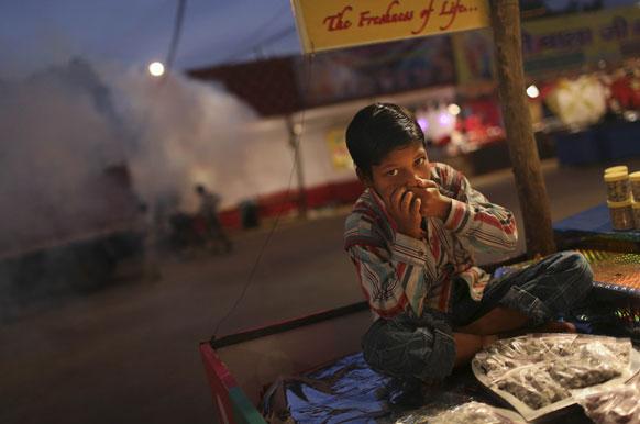 नई दिल्ली में धुएं से बचाव की कोशिश करता एक लड़का।