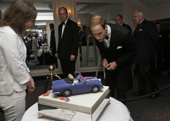 ब्रिटेन के राजकुमार प्रिंस विलियम्स एक वेडिंक केक को देखते हुए।