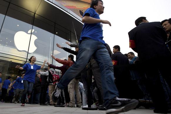 बीजिंग में एपल के न्यू स्टोर से बाहर कस्टमर से चियर करते चीनी कर्मचारी।