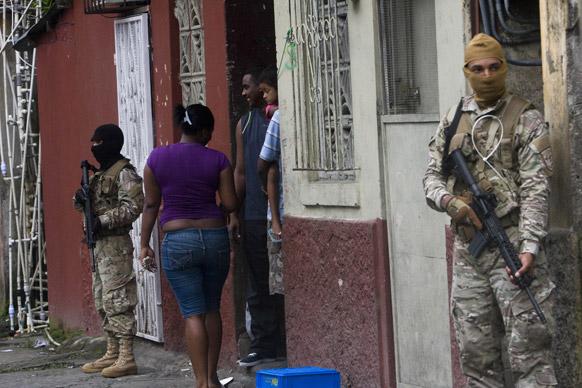 पनामा के कोलोन में लोगों की सुरक्षा में तैनात सुरक्षाकर्मी।