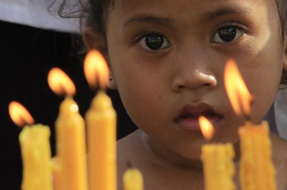 कम्बोडिया में पूर्व किंग नोरोडोम शिहानुक के लिए आयोजित प्रार्थना सभा को देखता एक बच्चा।