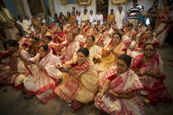 कोलकाता में दुर्गा पूजा के मौके पर बैठे हुए सिल परिवार के लोग।