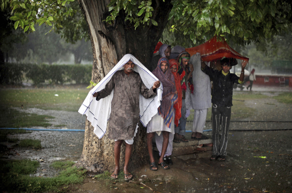 नई दिल्ली में बारिश के बीच एक पेड़ के नीचे शरण लेता हुआ एक व्यक्ति।