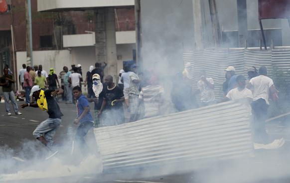 पनामा के कोलोन में विरोध-प्रदर्शन के दौरान अश्रु गैस के बीच मेटल की एक शीट ले जाते हुए प्रदर्शनकारी।