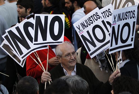 स्पेन में संसद के बाहर बजट कट संबंधी एक डिबेट के दौरान लोगों के बीच बैनर को वितरित करता एक व्यक्ति।