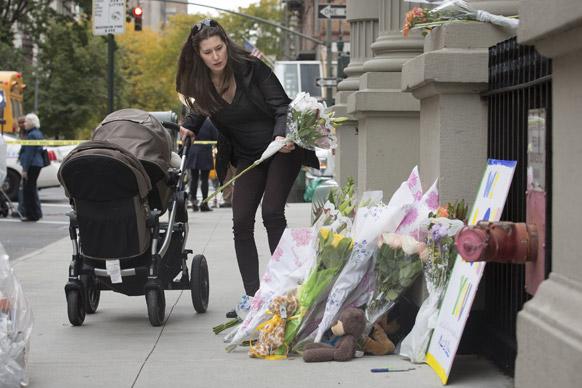 न्यूयार्क में एक स्मारक पर फूल चढ़ाती महिला।