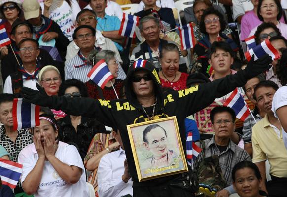 बैंकॉक में थाई प्रदर्शनकारी गले में राज भूमिबोल अद्युदेज की तस्वीर लटकाकर प्रदर्शन करते हुए।