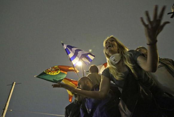 एथेंस की संसद के सामने सरकारी नीतियों के खिलाफ विरोध- प्रदर्शन करते लोग।