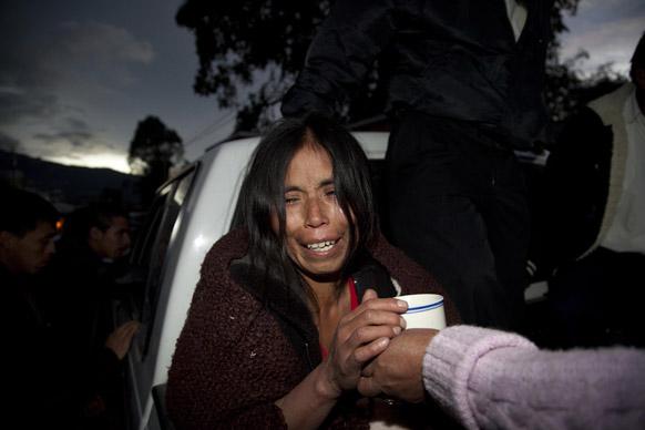 ग्वाटेमाला में भूकंप के बाद प्रभावित महिला को कुछ खाने-पीने को देते लोग।