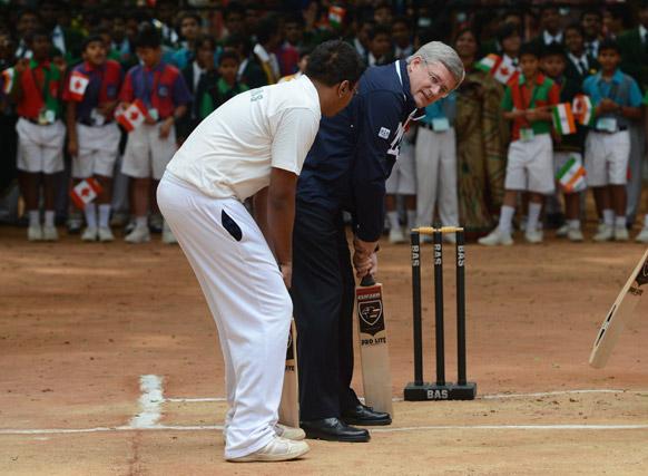 बेंगलुरु के बिशप कॉटन ब्वॉयज और गर्ल्स स्कूल में क्रिकेट बल्ले पर हाथ आजमाते हुए प्रधानमंत्री स्टीफन हॉर्पर।