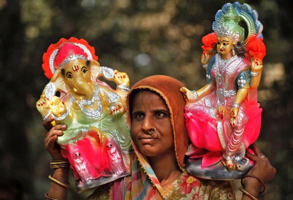 दीपावली के मौके पर इलाहाबाद में गणेश-लक्ष्मी की मूर्ति बेचने के लिए जे जाती एक महिला।