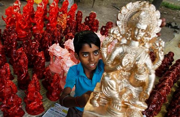 इलाहाबाद में दीपावाली पर्व से पहले माता लक्ष्मी की प्रतिमा को तैयार कर उसे बेचता एक बाल मूर्तिकार।