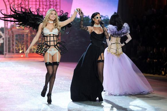 विक्टोरिया सीक्रेट फैशन शो के दौरान रनवे पर मॉडल डाउजेन क्रोएस के साथ प्रस्तुति देते हुए गायिका रिहाना।