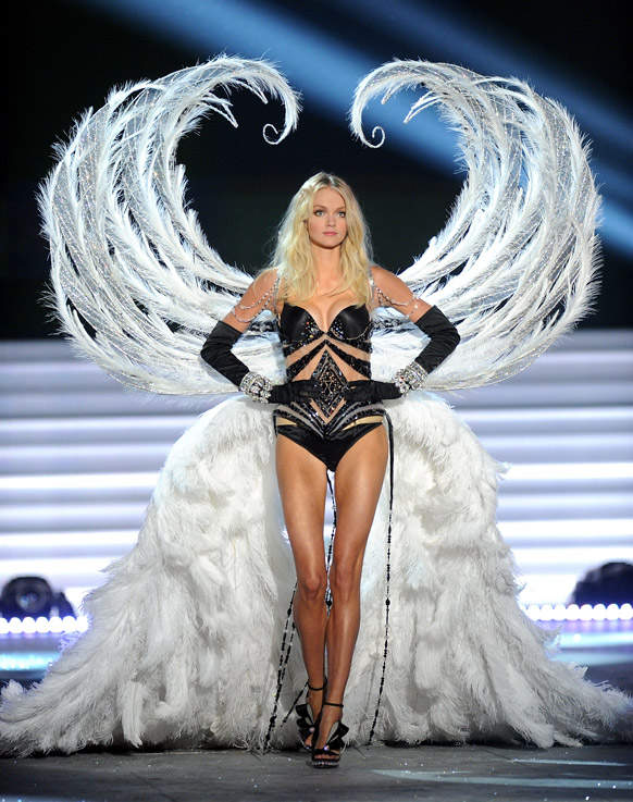 विक्टोरिया सीक्रेट फैशन शो 2012 के दौरान आकर्षक परिधान में एक मॉडल रैंप पर चलते हुए।
