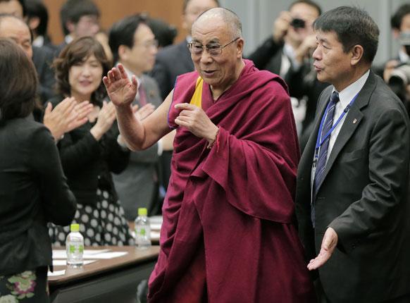 टोक्यो में एक सेमिनार में हिस्सा लेने जाते हुए तिब्बती धर्म गुरू दलाई लामा।