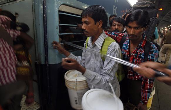 छठ पूजा के अवसर पर नई दिल्ली से बिहार जाने वाली ट्रेन में चढ़ते यात्री।