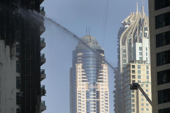 दुबई की एक इमारत में लगी आग को बुझाते अग्निशमनकर्मी।