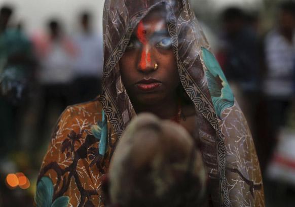 नई दल्ली में छठ की पूजा के दौरान अर्घ्य देती एक श्रद्धालु ।
