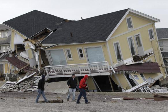 न्यूयार्क में क्षतिग्रस्त मकान को देखते हुए कुछ व्यक्ति।