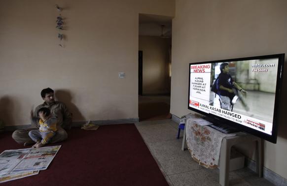 टीवी पर कसाब को फांसी दिए जाने की खबर देखता एक व्यक्ति।