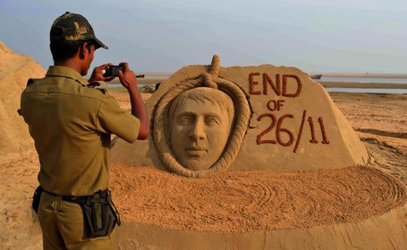 उड़ीसा के बालासोर में कसाब की बनाई रेत की प्रतिमा की फोटोग्राफी करता पुलिसकर्मी।
