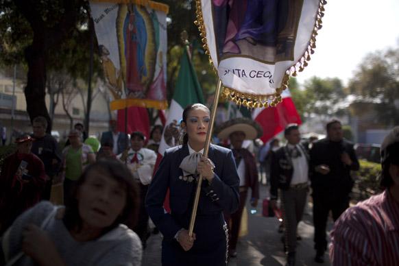 मेक्सिको सिटी में संत कसिला की तस्वीर के साथ प्रदर्शन करते लोग।