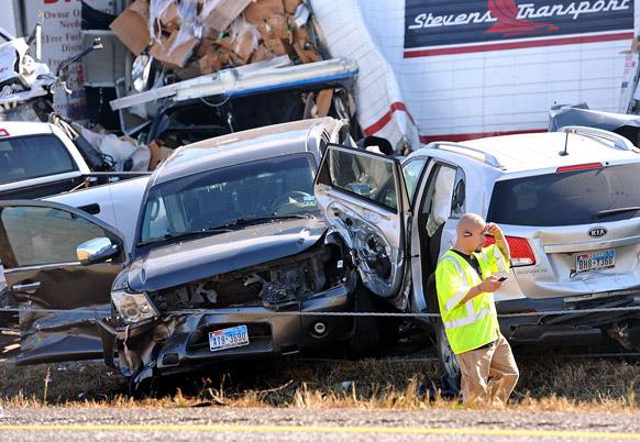 टेक्सास में वाहनों के ढेर के पास से गुजरता एक आपातकर्मी।