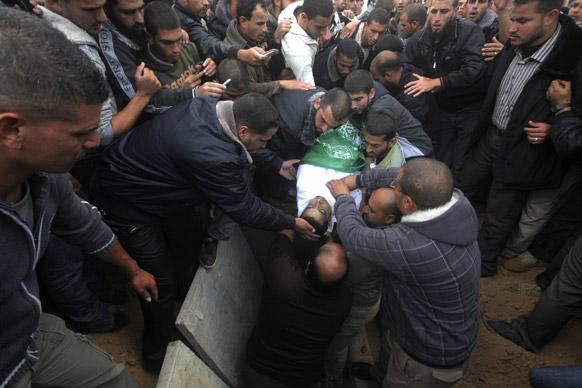 गाजा पट्टी के खान यूनिस में एक शव को दफनाते लोग।