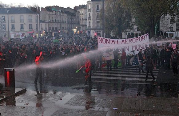 फ्रांस के पश्चिम हिस्से में प्रदर्शनकारियों को तितर-बितर करने के लिए पानी की बौछार करती पुलिस।