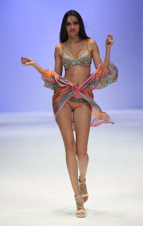 सिंगापुर में वुमन फैशन वीक के दौरान डिजाइनर सिलवियन इम्वर्ग का क्रिएशन पेश करती हुई मॉडल।