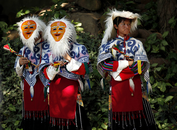 बेंगलुरू में अपने आध्यात्मिक गुरु दलाई लामा का स्वागत करने के लिए पारंपरिक परिधान में तिब्बती छात्र।