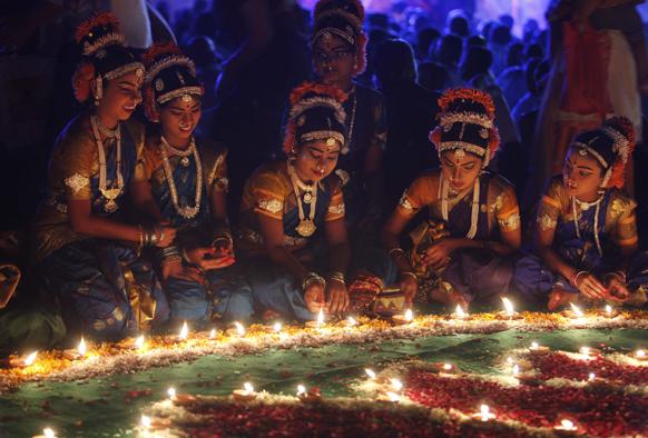 हैदराबाद में कार्तिक सोमावरम के उपलक्ष्य में मिट्टी के दीप जलातीं लड़कियां।